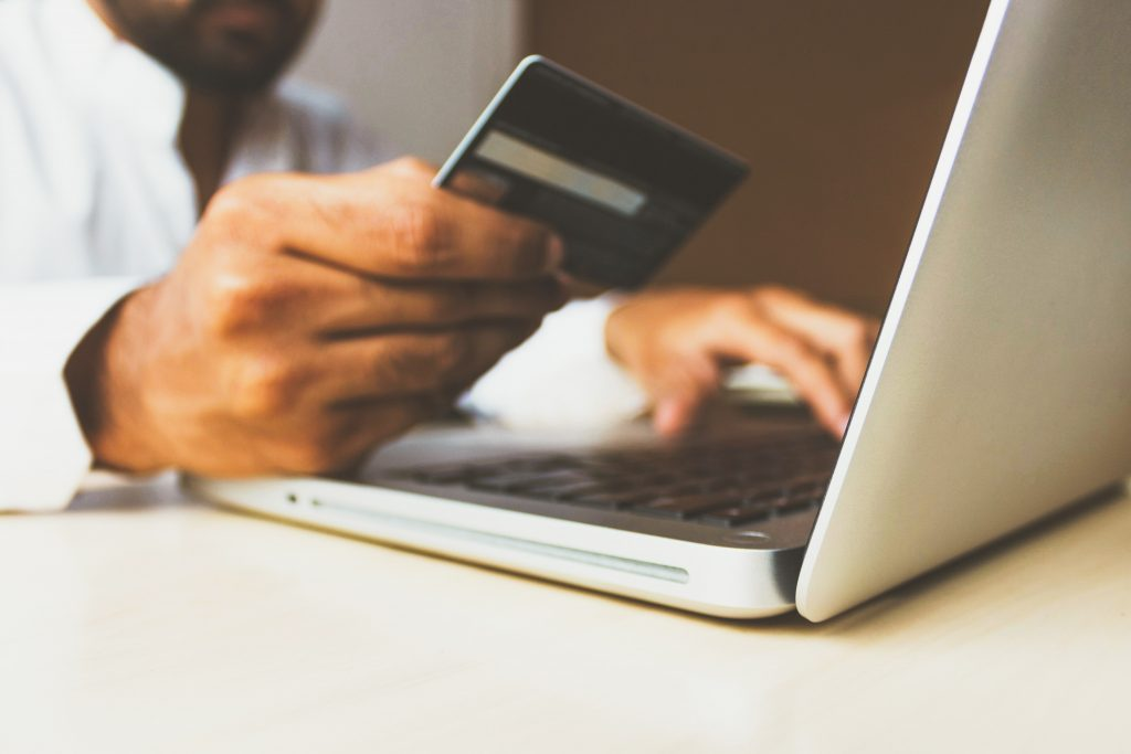 businessman holds credit card on laptop